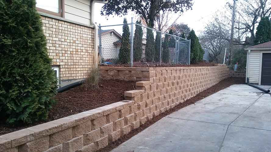 Image of finished retaining wall, beside driveway